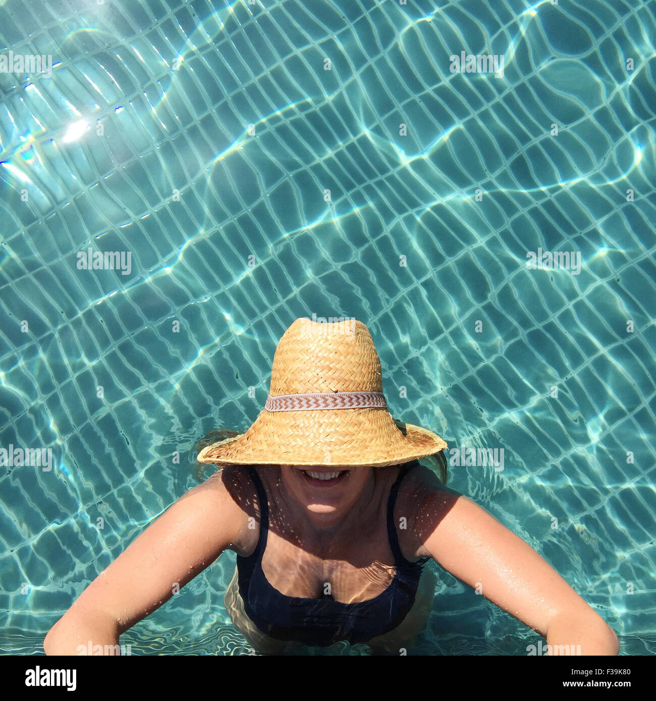 Woman standing in swimming pool looking up - Stock Image