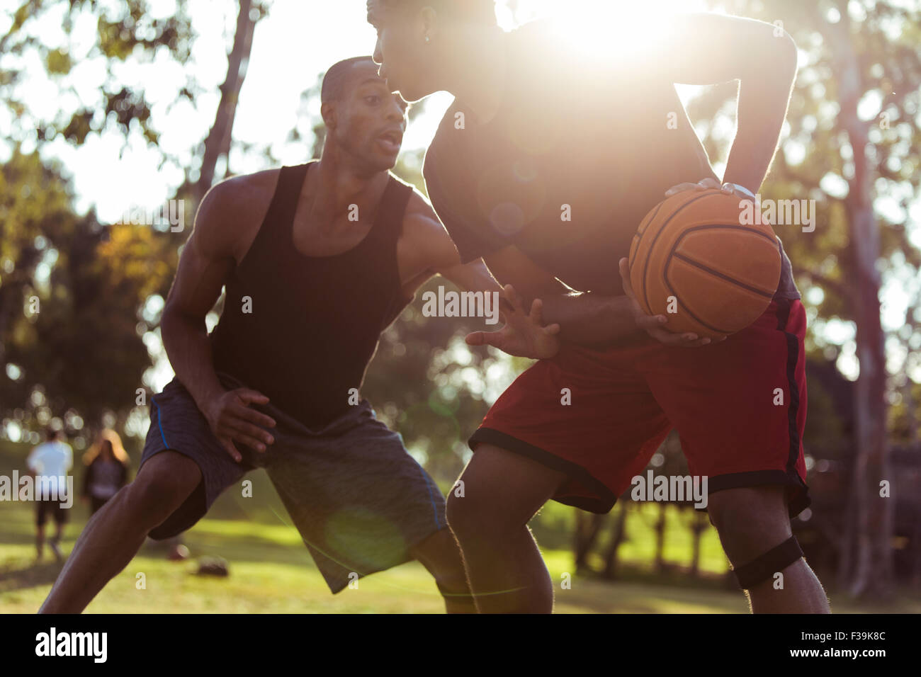 Two young men playing basketball in the park at sunset Stock Photo