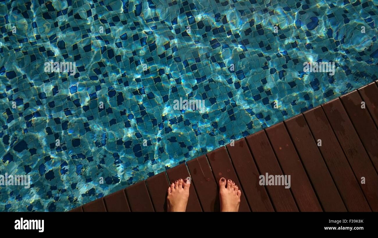 Close-up of woman's feet by a swimming pool - Stock Image