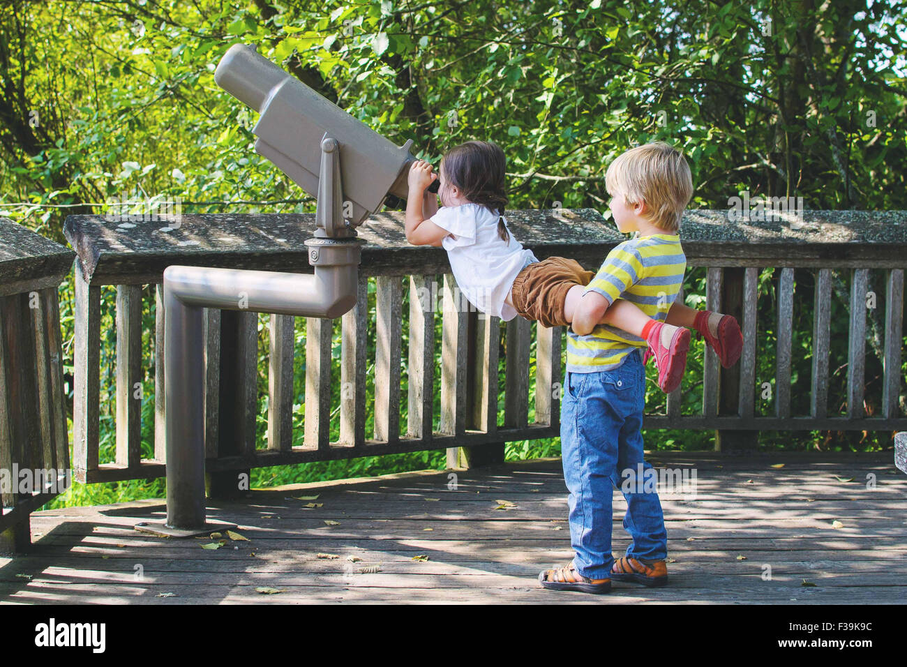 Boy lifting girl to look through telescope - Stock Image