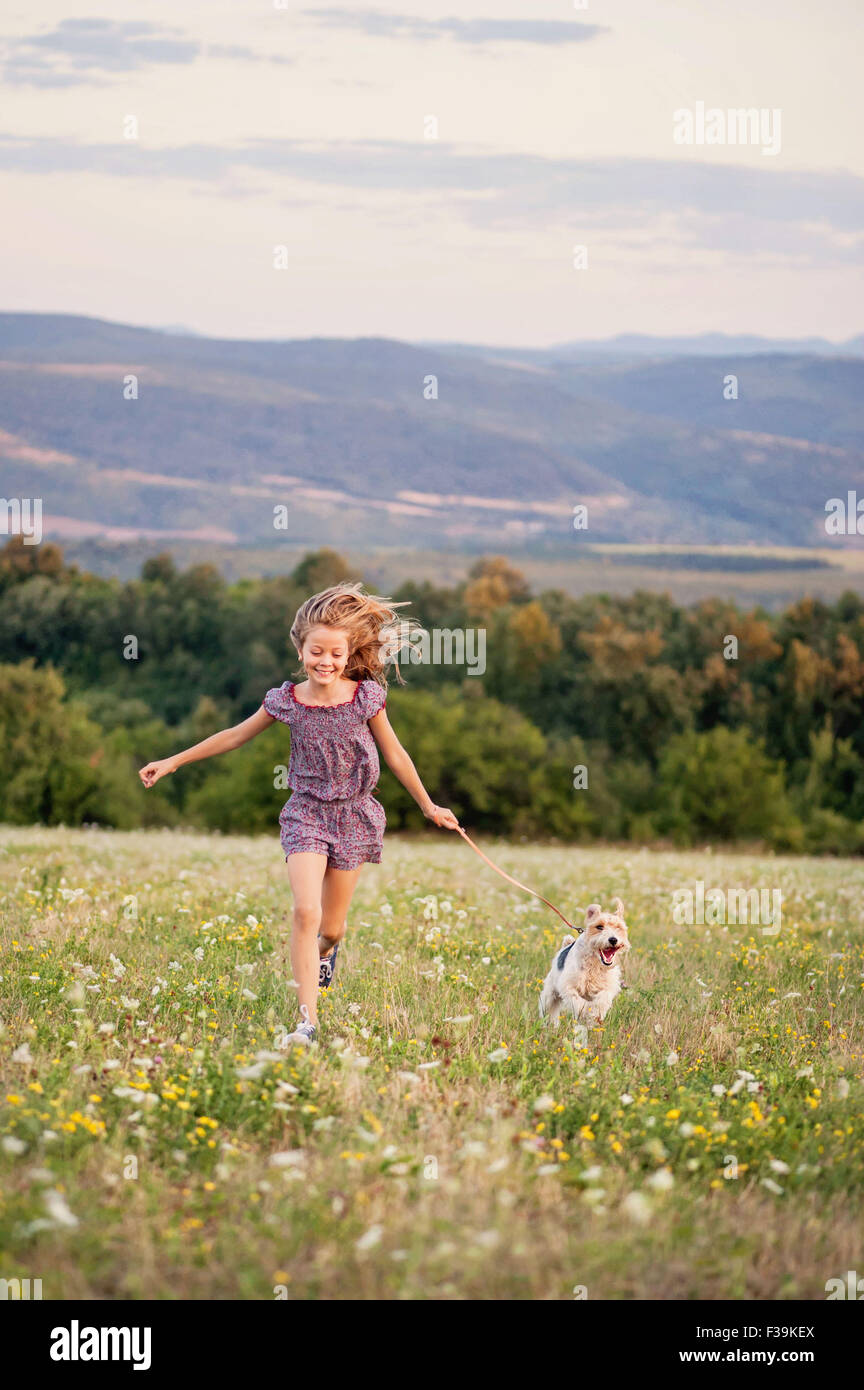 Portrait of a girl running with her fox terrier dog in a field - Stock Image