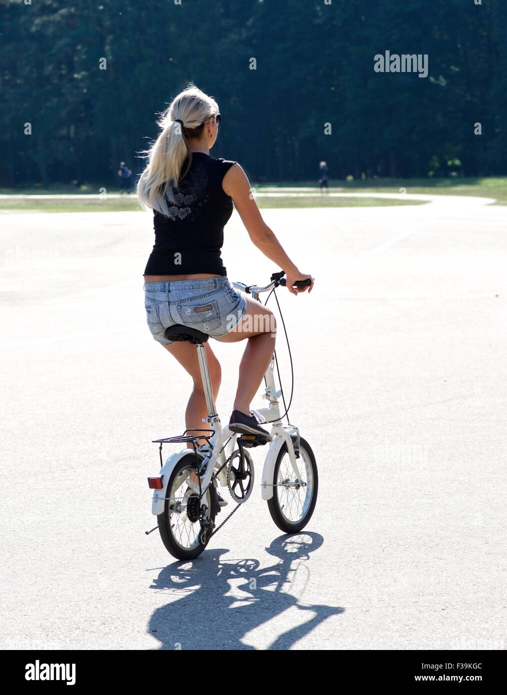 Rear view of a woman riding bicycle in the park, Lithuania - Stock Image