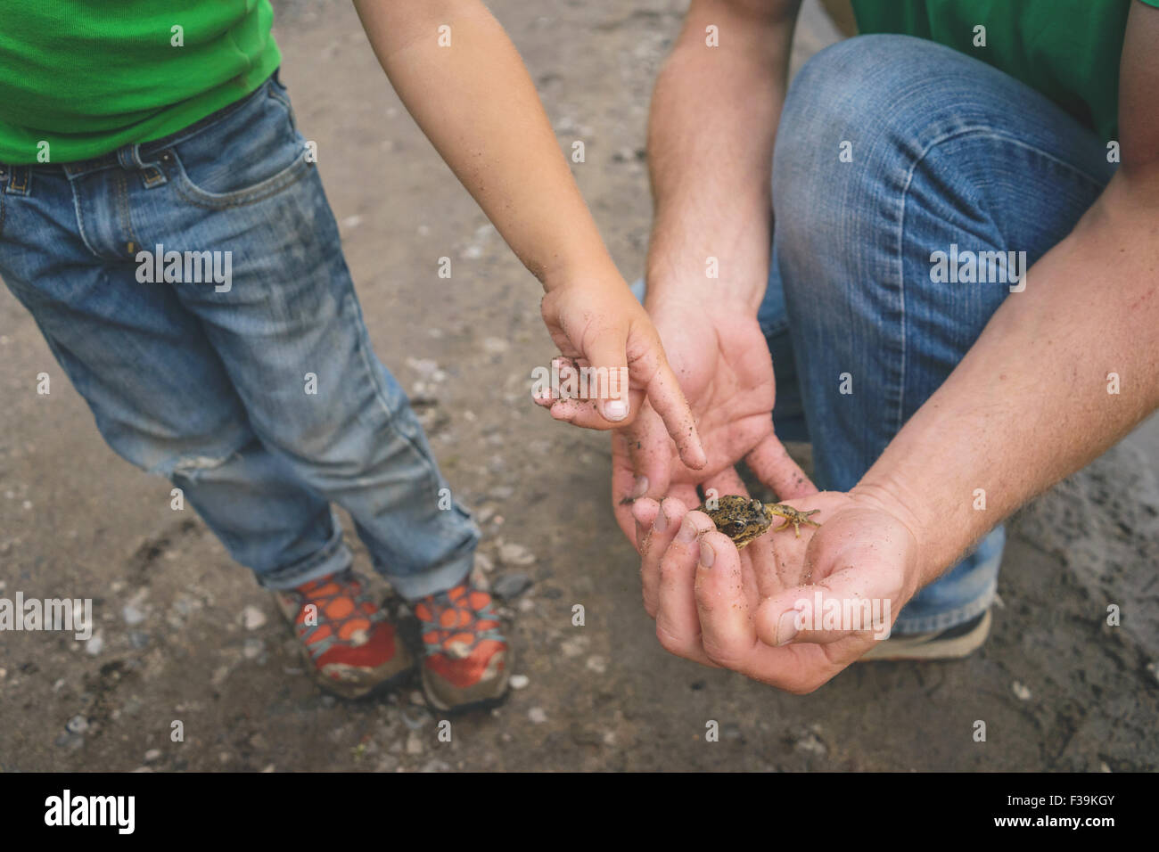 Boy pointing at a snail in his father's hands - Stock Image