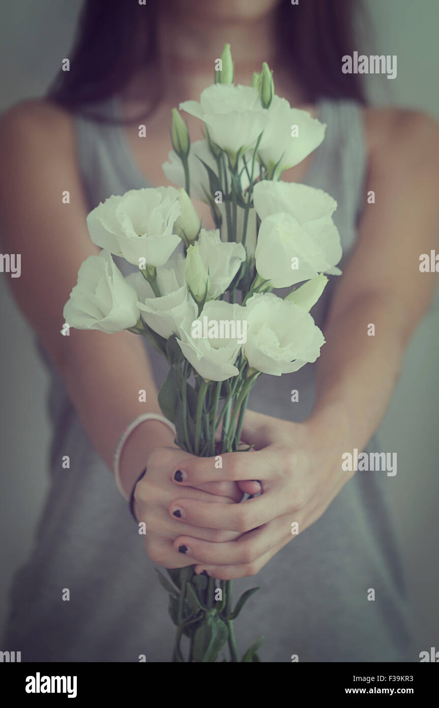 Mid section of a teenage girl holding a bunch of  flower - Stock Image