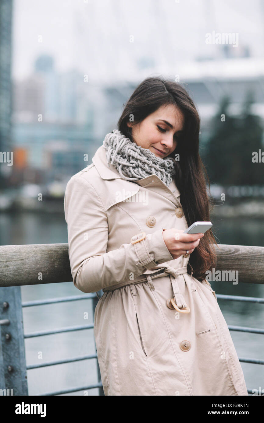 Portrait of a woman standing on a balcony looking at her mobile phone, smiling Stock Photo