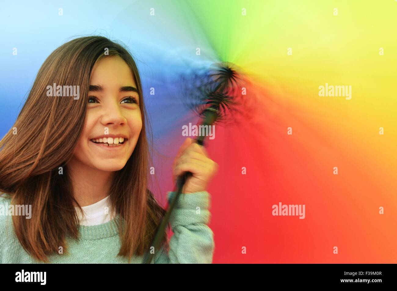 Portrait of a smiling girl twirling a multi-colored umbrella - Stock Image