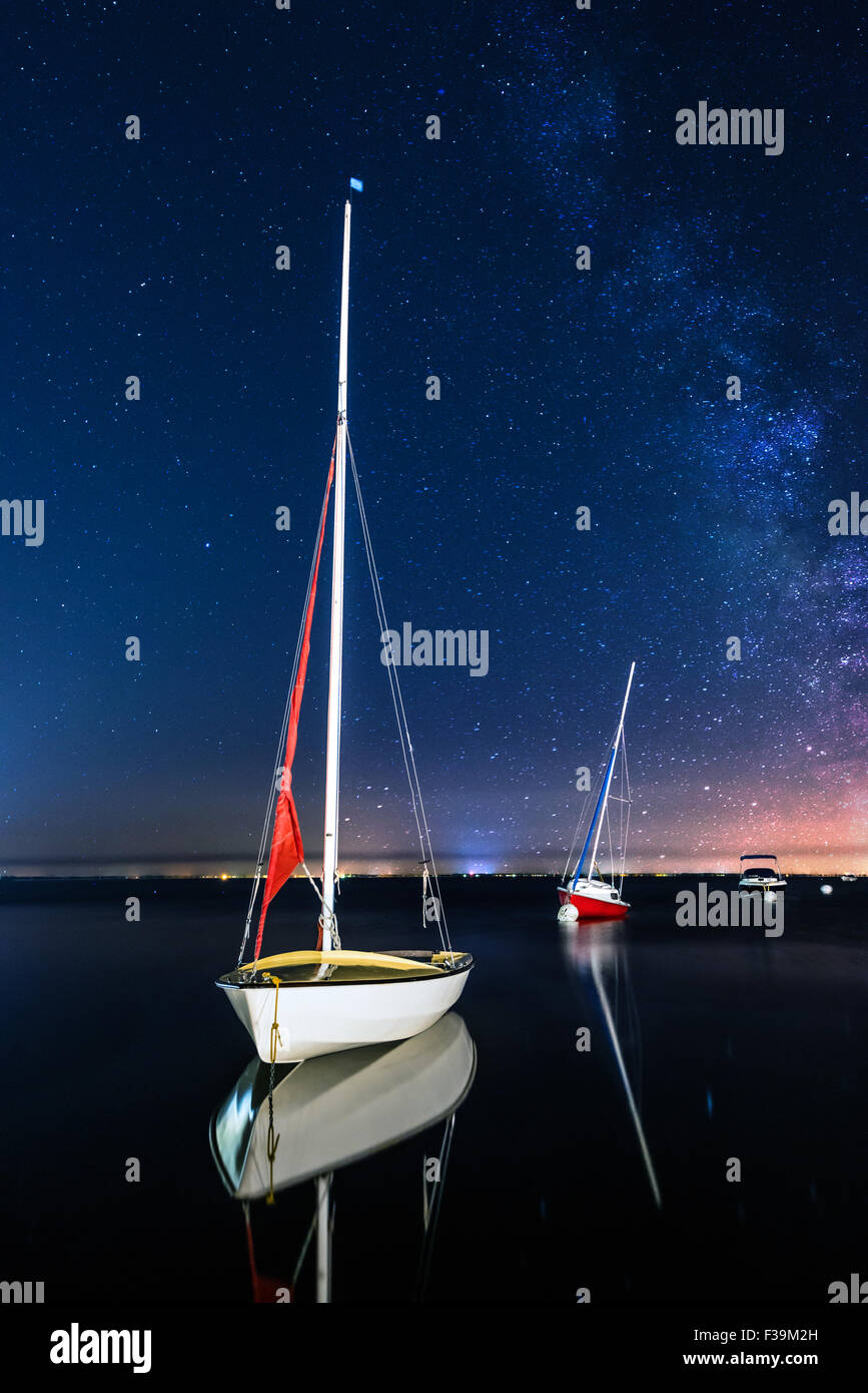 Three sailing boats anchored at night Stock Photo