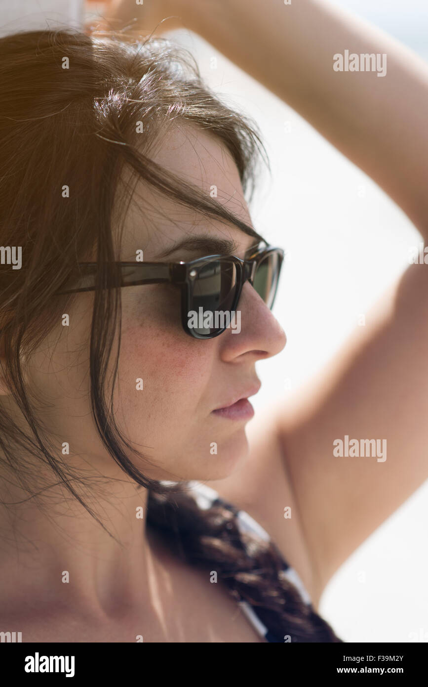Close-up portrait of a woman with raised arm  looking ahead - Stock Image