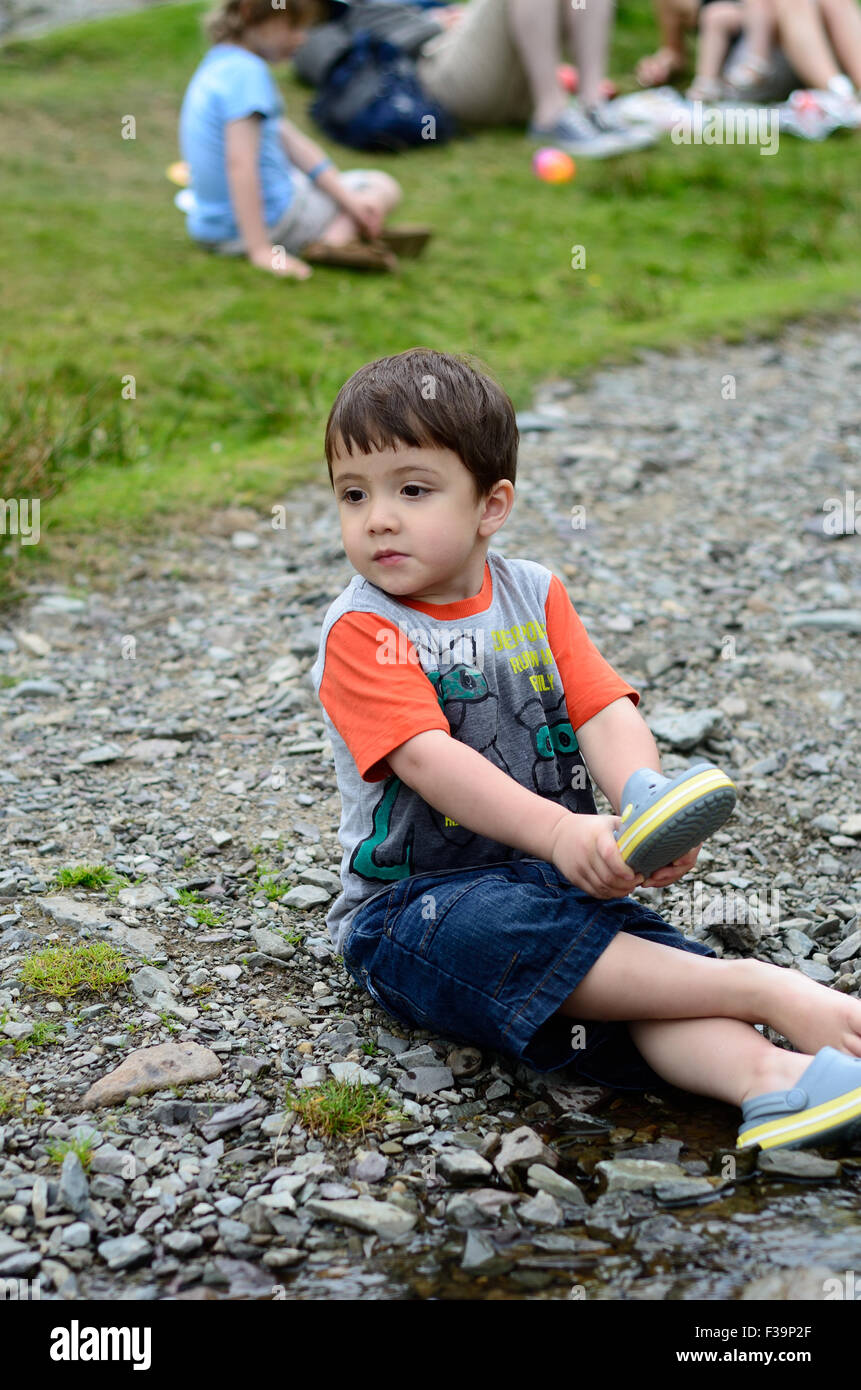 A young boy sits in the floor at the edge of a stream to get a stone out of his shoe. - Stock Image