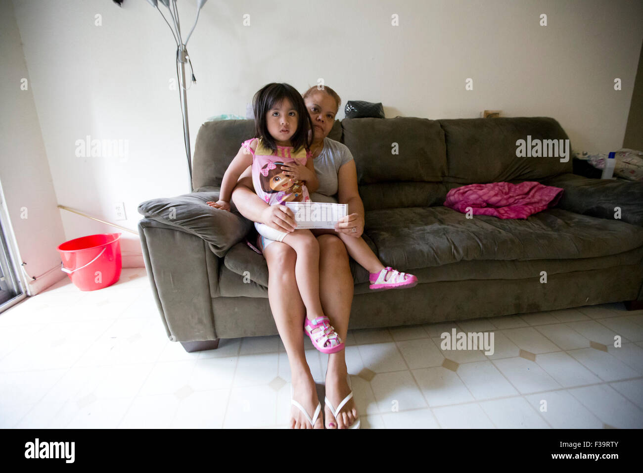 Silvia Jaimes and 3 year old Camila, a neighboor's daughter, inside her Lakeview Apartment home where she has - Stock Image