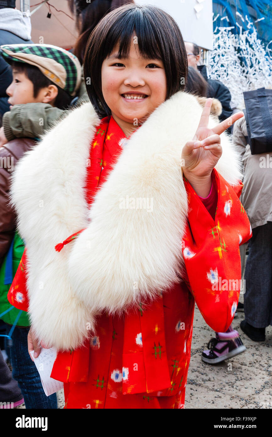 Japanese child, girl, 6-7 years old, smiling and giving peace gesture to viewer. Wear red kimono with white fur - Stock Image
