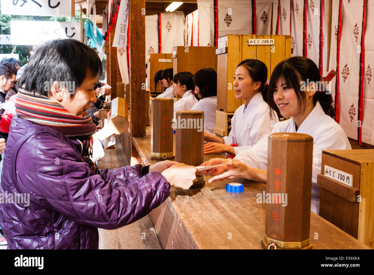 Japan, Nishinomiya shrine, New year Day, Shogatsu. Woman buying omikuji fortune papers from Miko, shrine maiden, - Stock Image