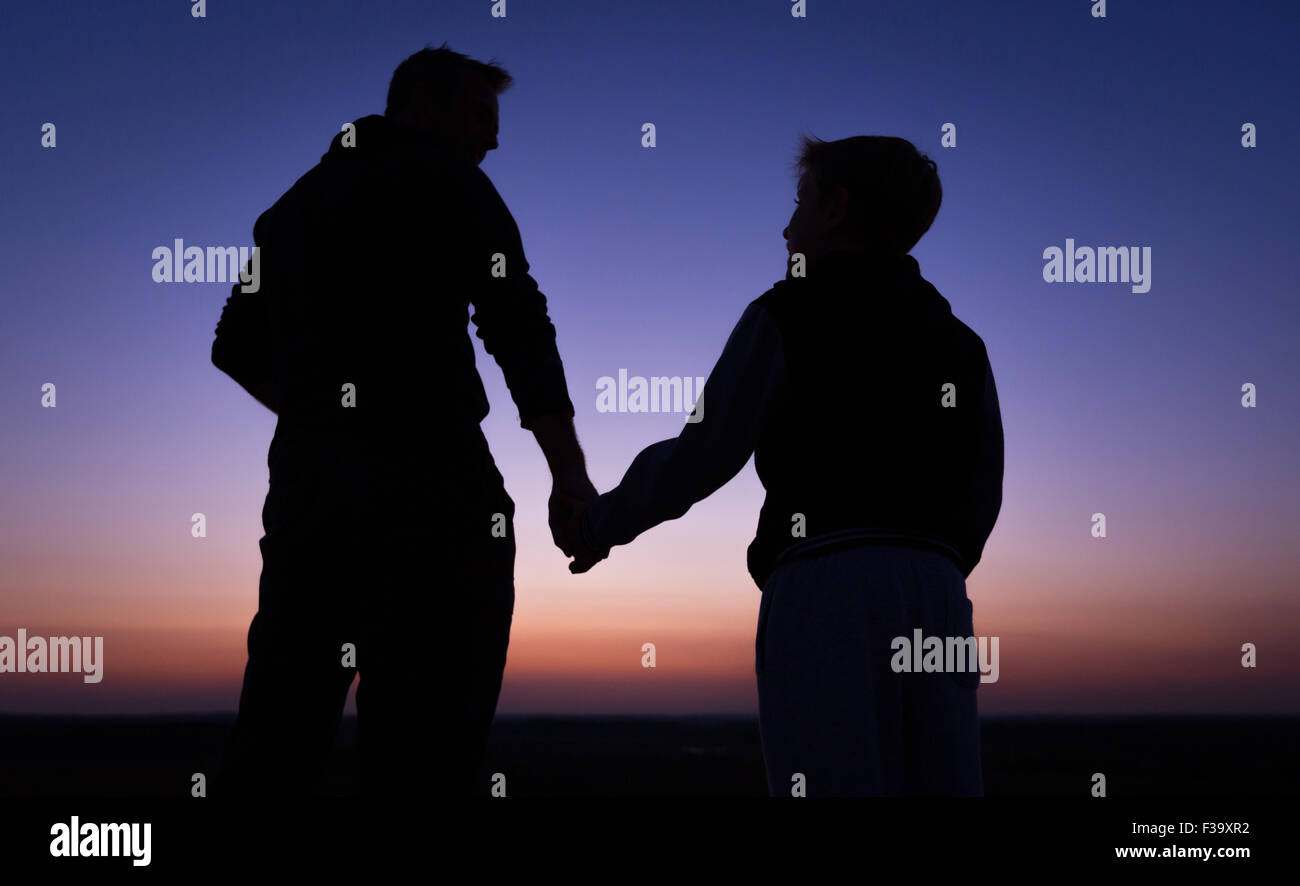 Fostering and parenting concept photo of a father and son in silhouette holding hands watching the sunset - Stock Image