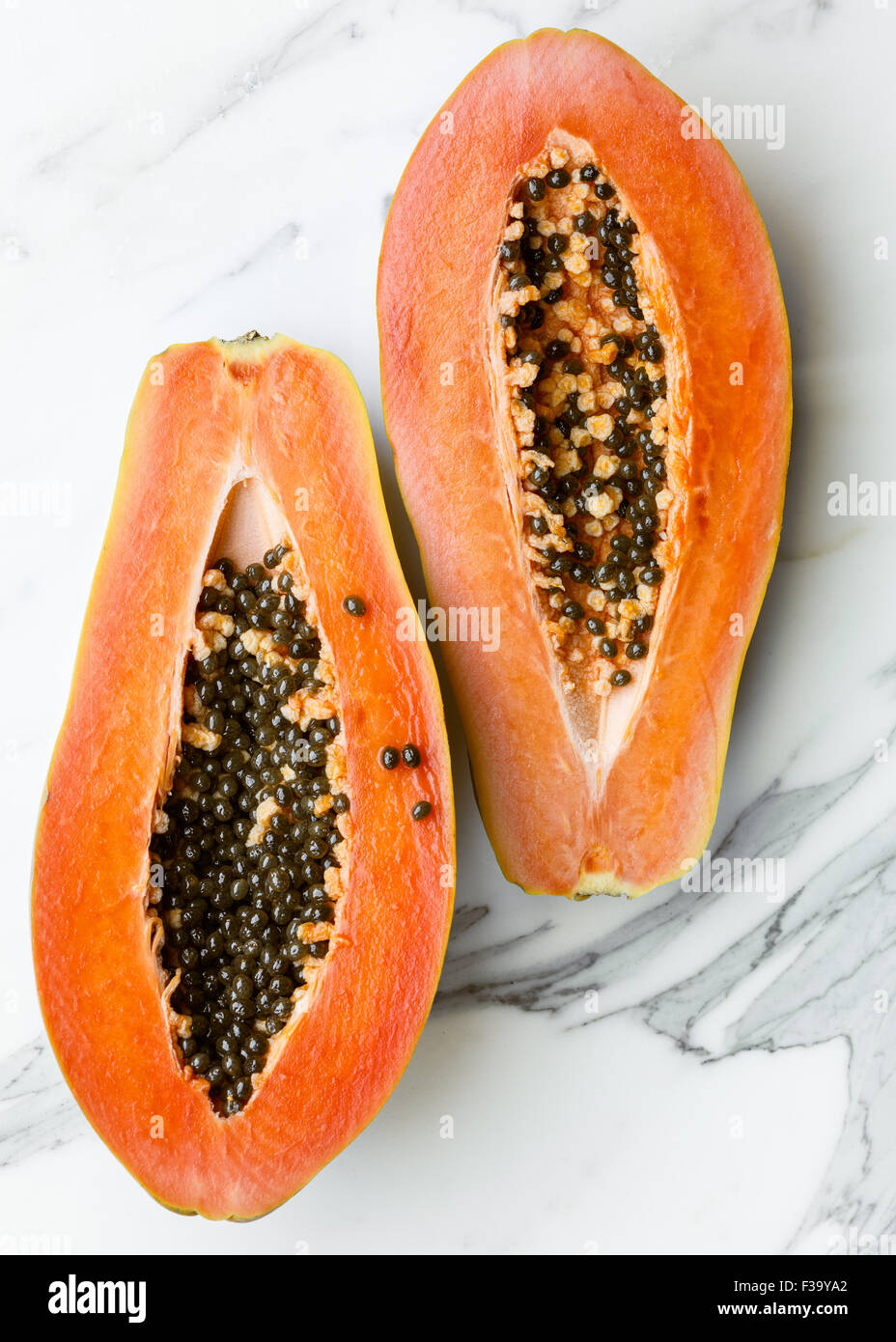 A Papaya cut in half on marble surface Stock Photo