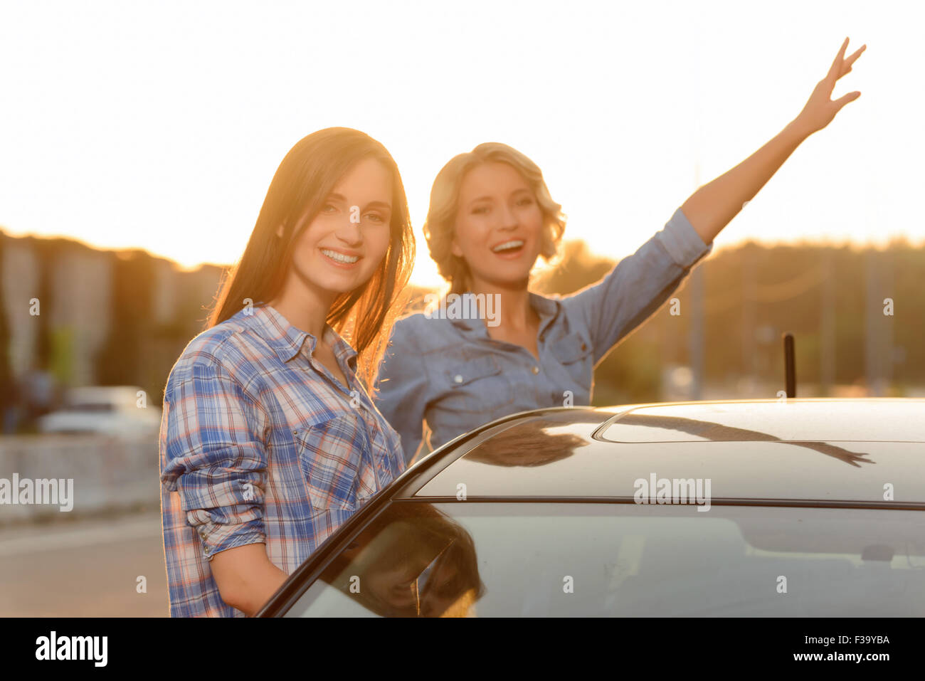 Nice time. Upbeat appealing smiling girls standing near the car and expressing positivity while going to ride - Stock Image