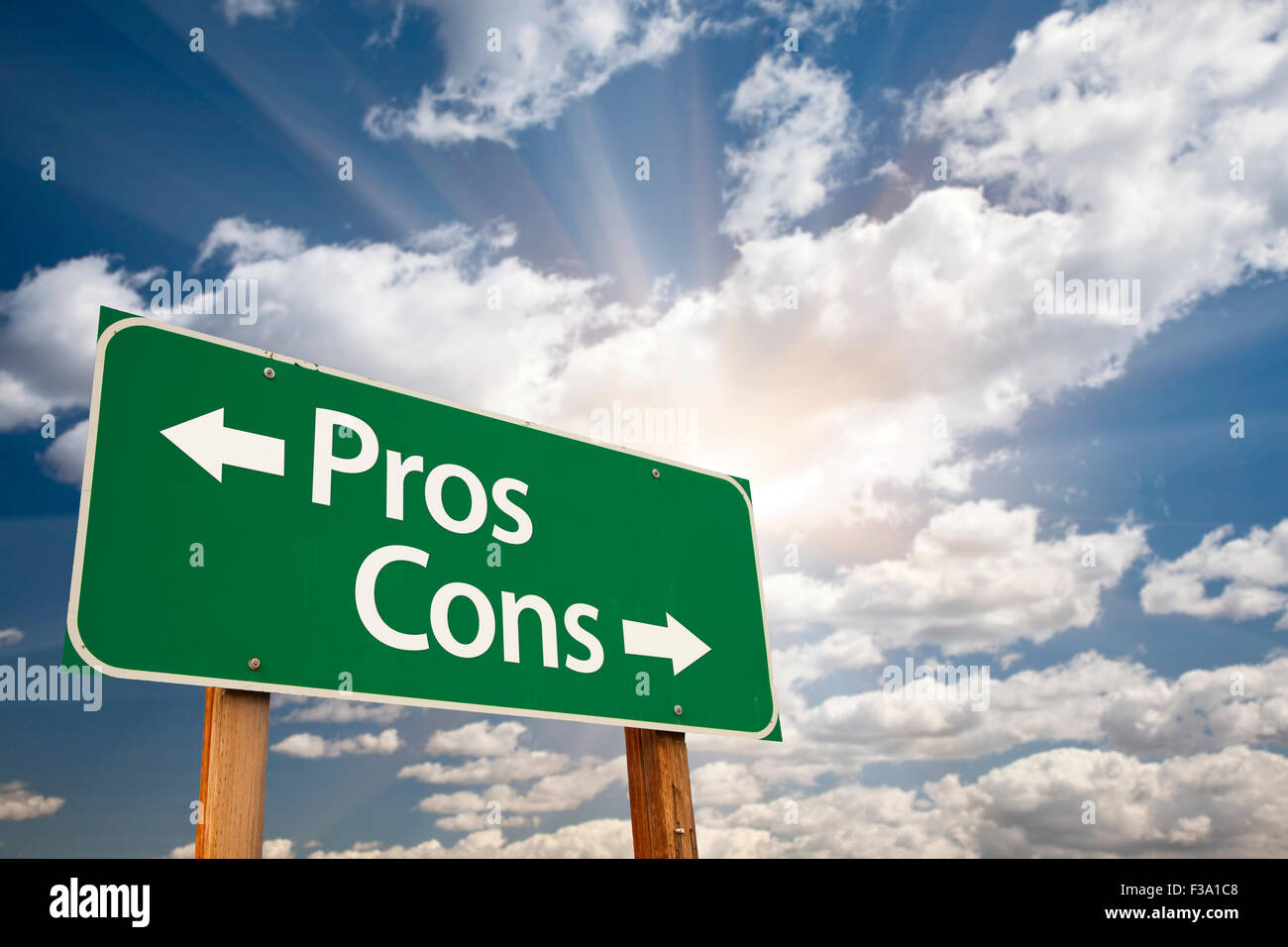 Pros and Cons Green Road Sign With Dramatic Clouds and Sky. - Stock Image