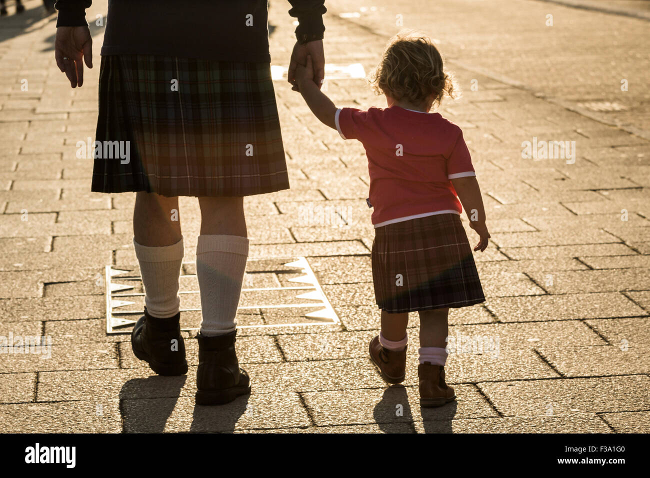 Rear view of man and child wearing kilts; national dress of Scotland. Stock Photo