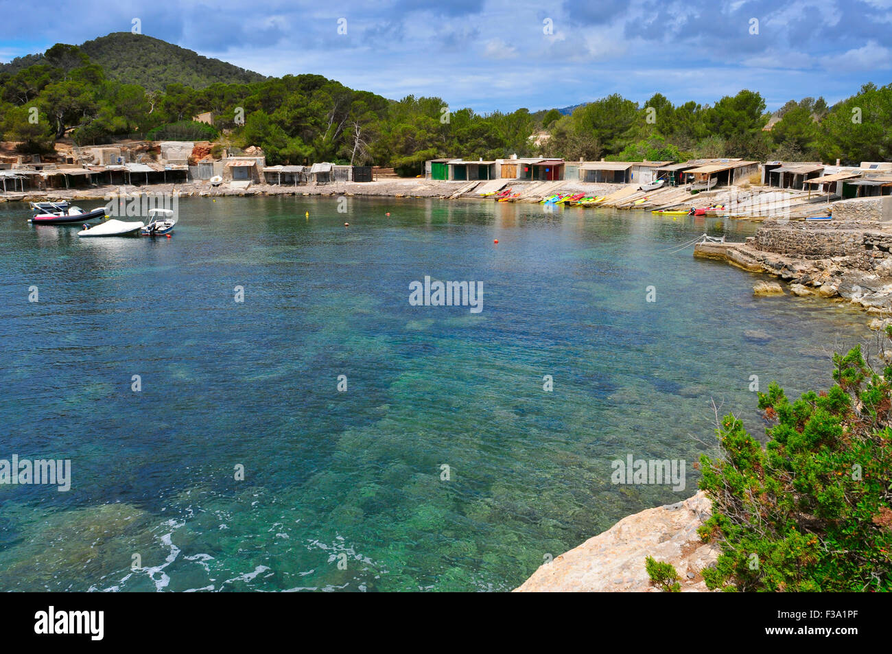 a view of the Sa Caleta cove in Ibiza Island, Spain, with its traditional fishermen shelters - Stock Image