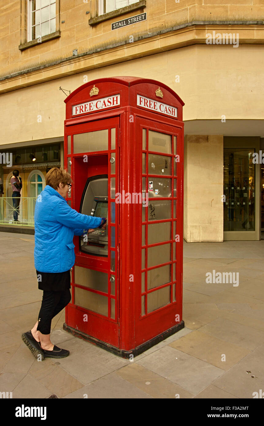 Red telephone box converted to a cash point ATM - Stock Image