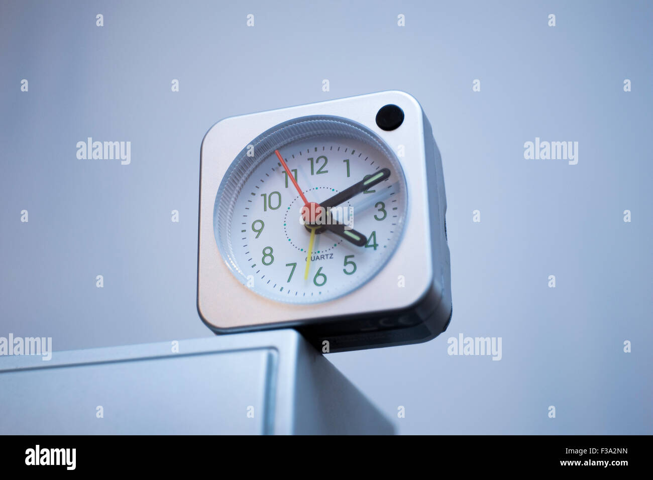 square clock on the edge running out of time - Stock Image