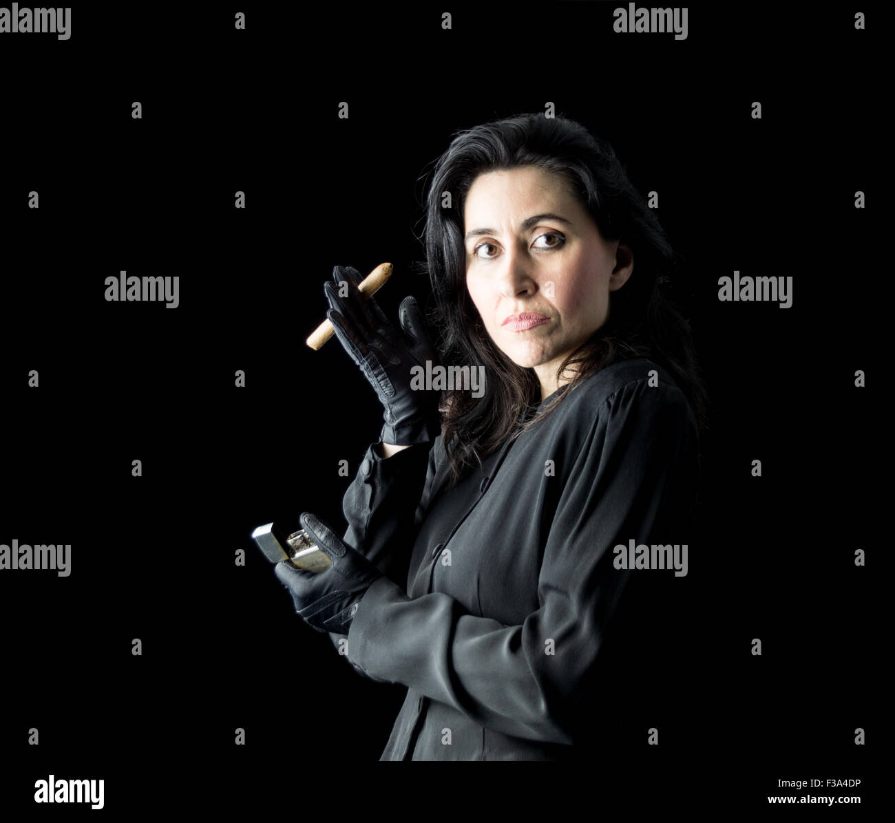 Brunette woman in black dress and black gloves holding a cigar in one hand and a lighter in the other - Stock Image