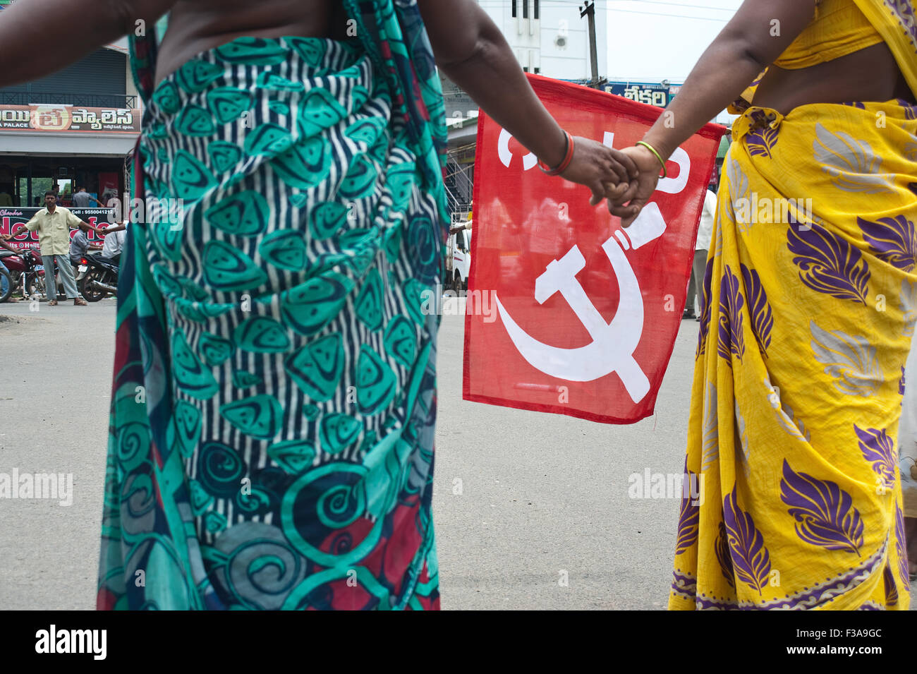 Municipal workers are on strike. One woman is holding a flag with the communist logo ( India) - Stock Image