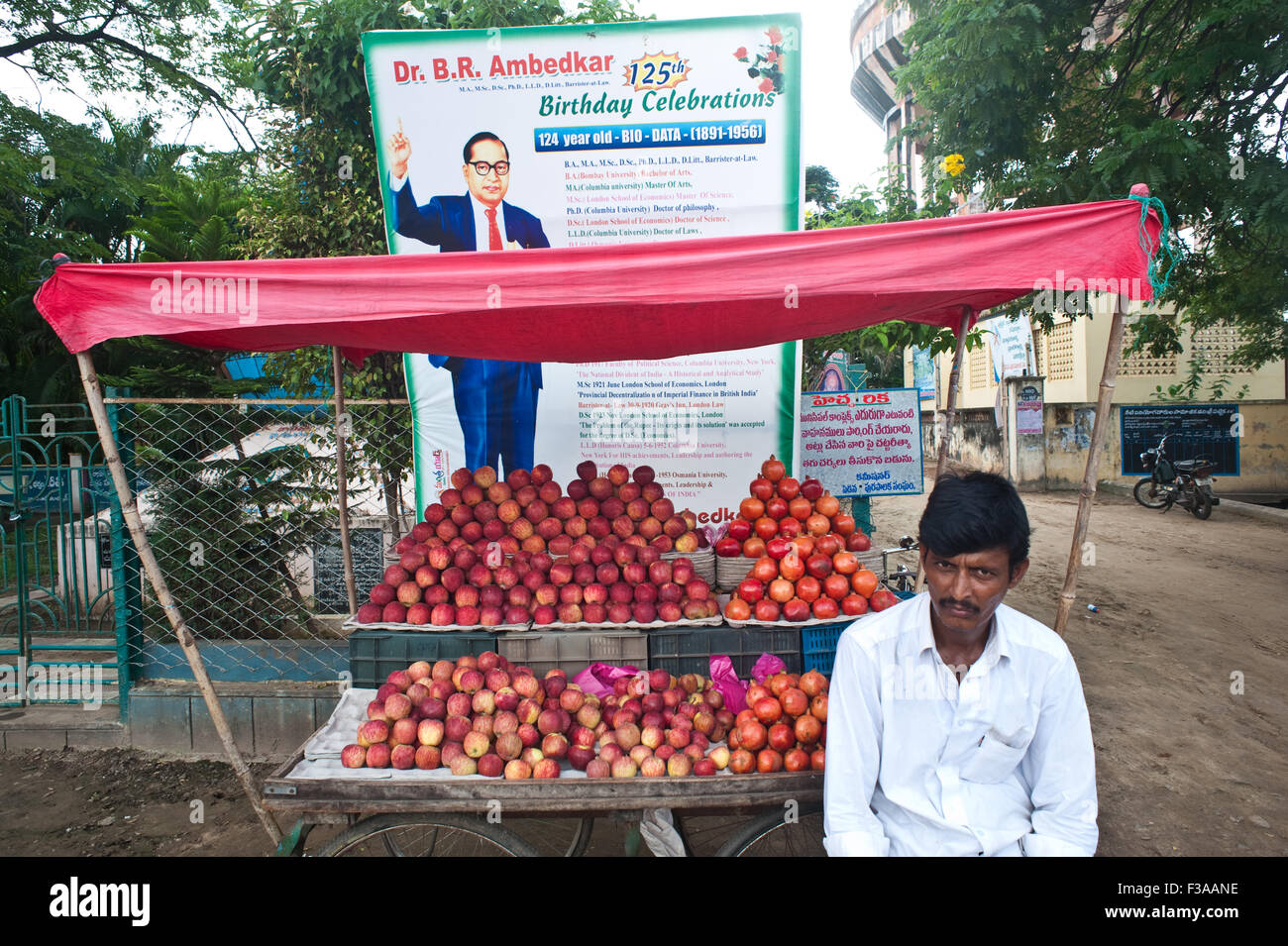 Man selling apples and pomegranates in front of a billboard commemorating B.R. Ambedkar, a renowned indian politician - Stock Image