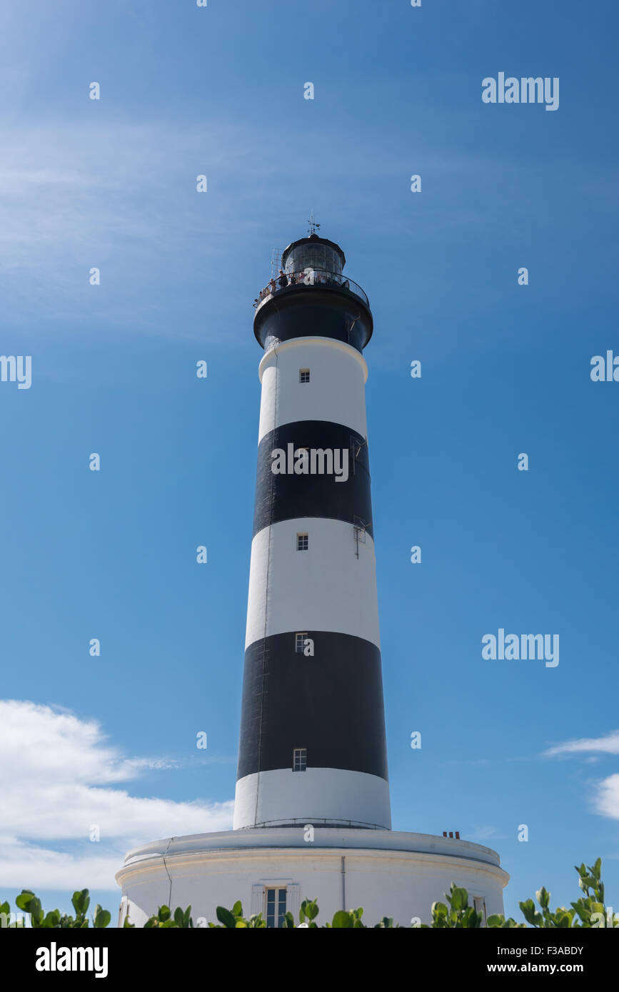 Black and white lighthouse isolated on a blue and cloudy sky - Stock Image