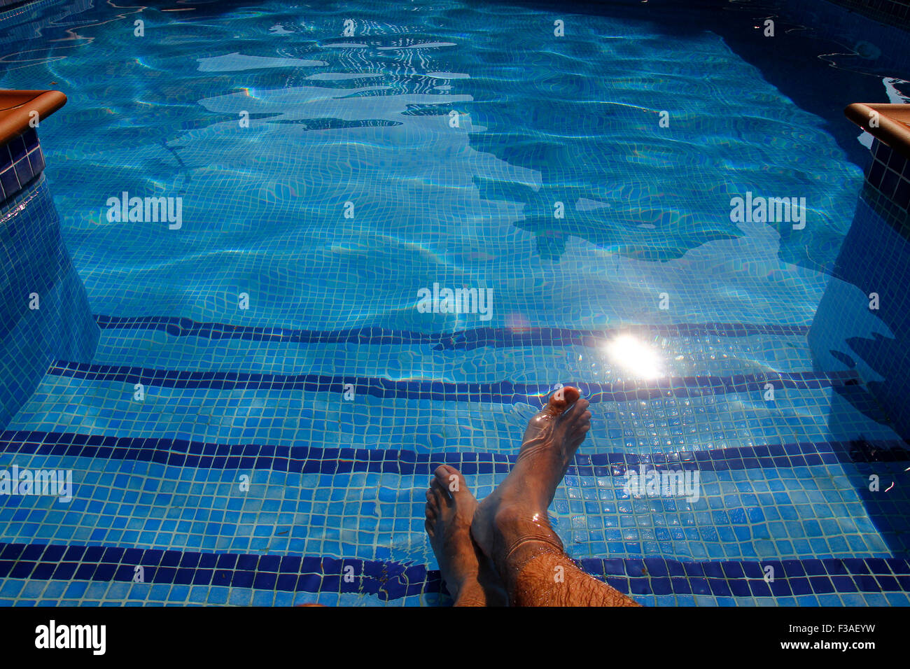 Human feet in a pool, transparent water - Stock Image