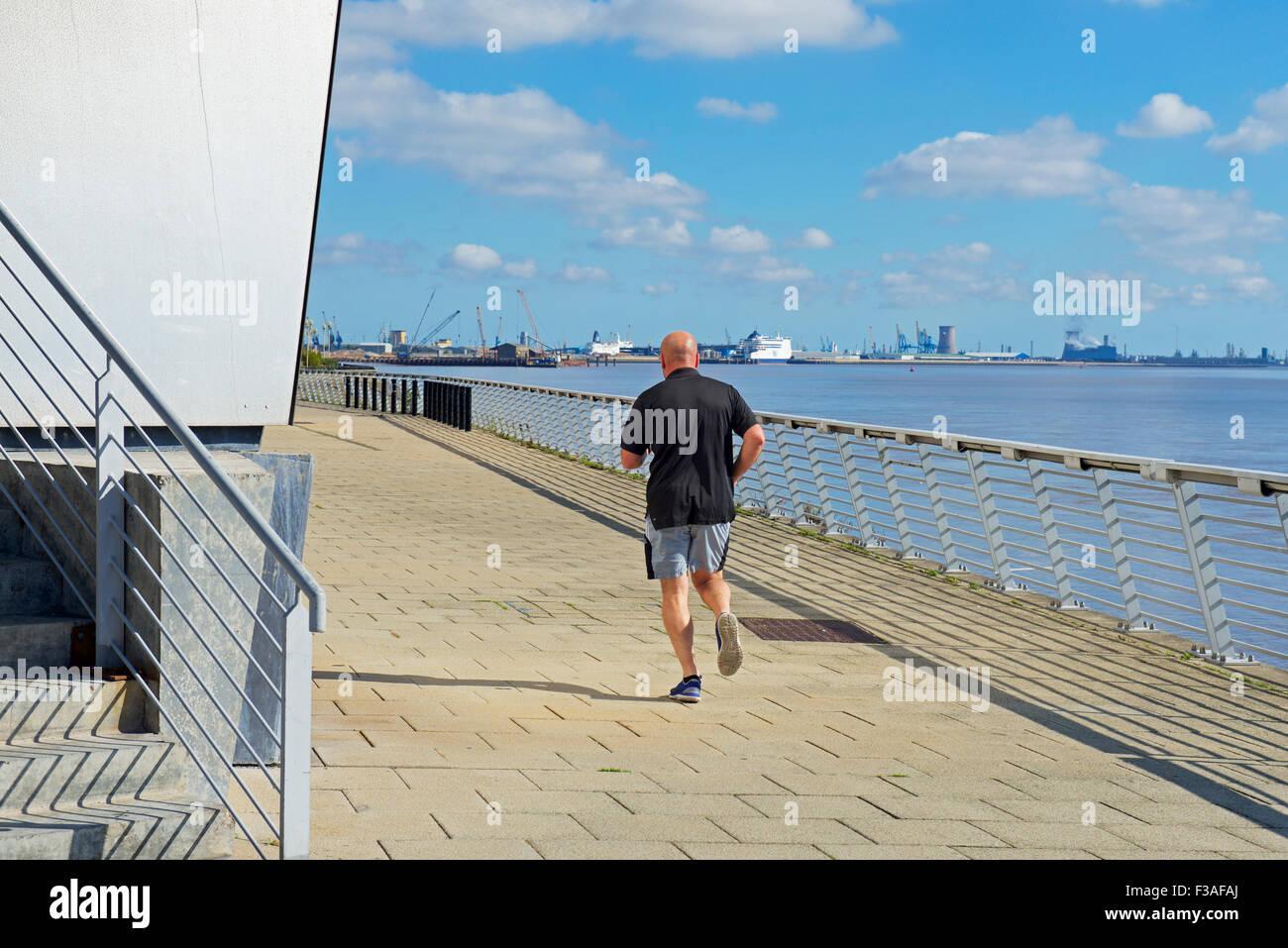 Man jogging on the promenade, Kingston upon Hull, East Riding of Yorkshire, England UK - Stock Image