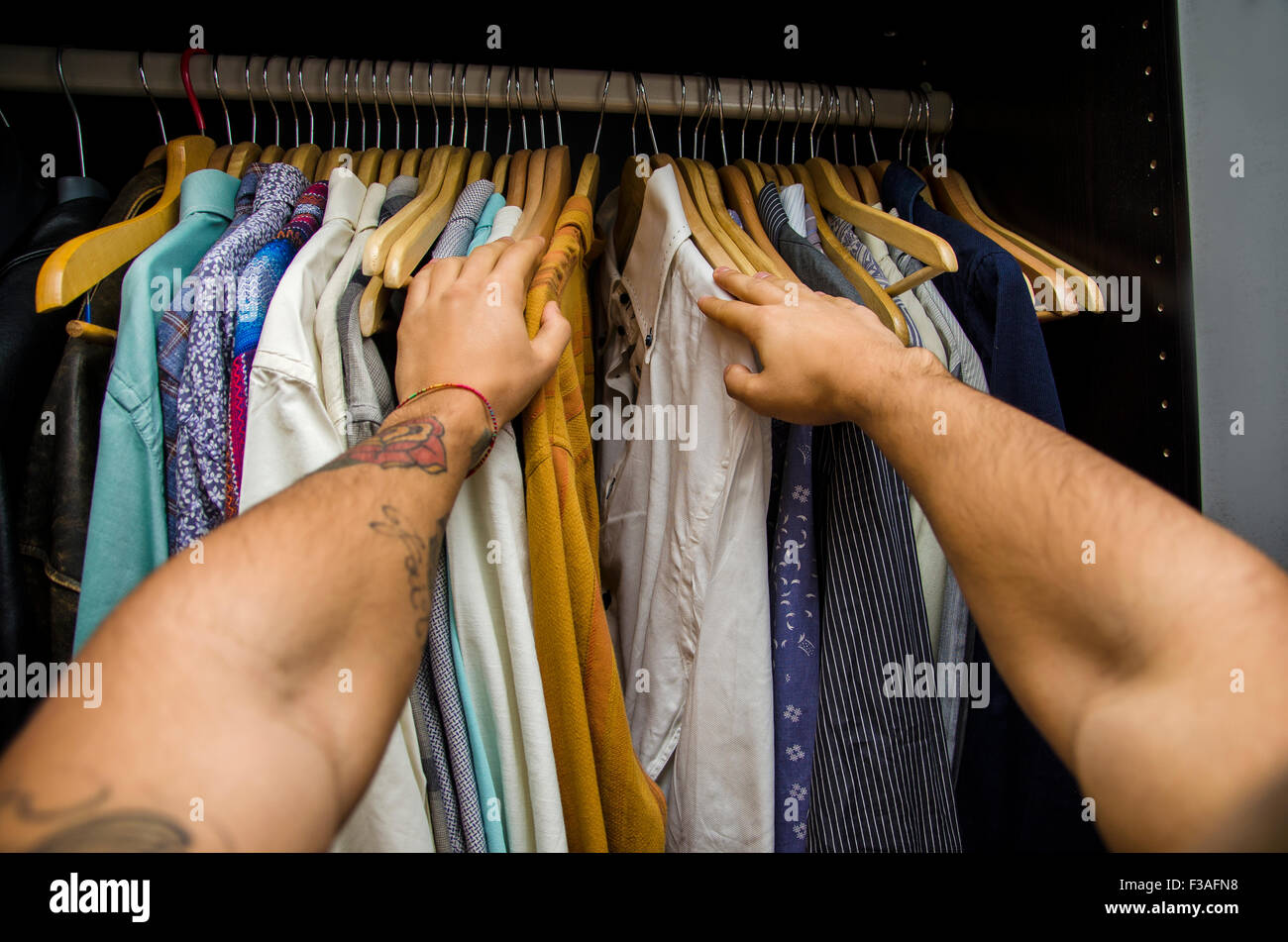 Man searching for a shirt hanging on the rail in his wardrobe, first person point of view looking down his arms. - Stock Image