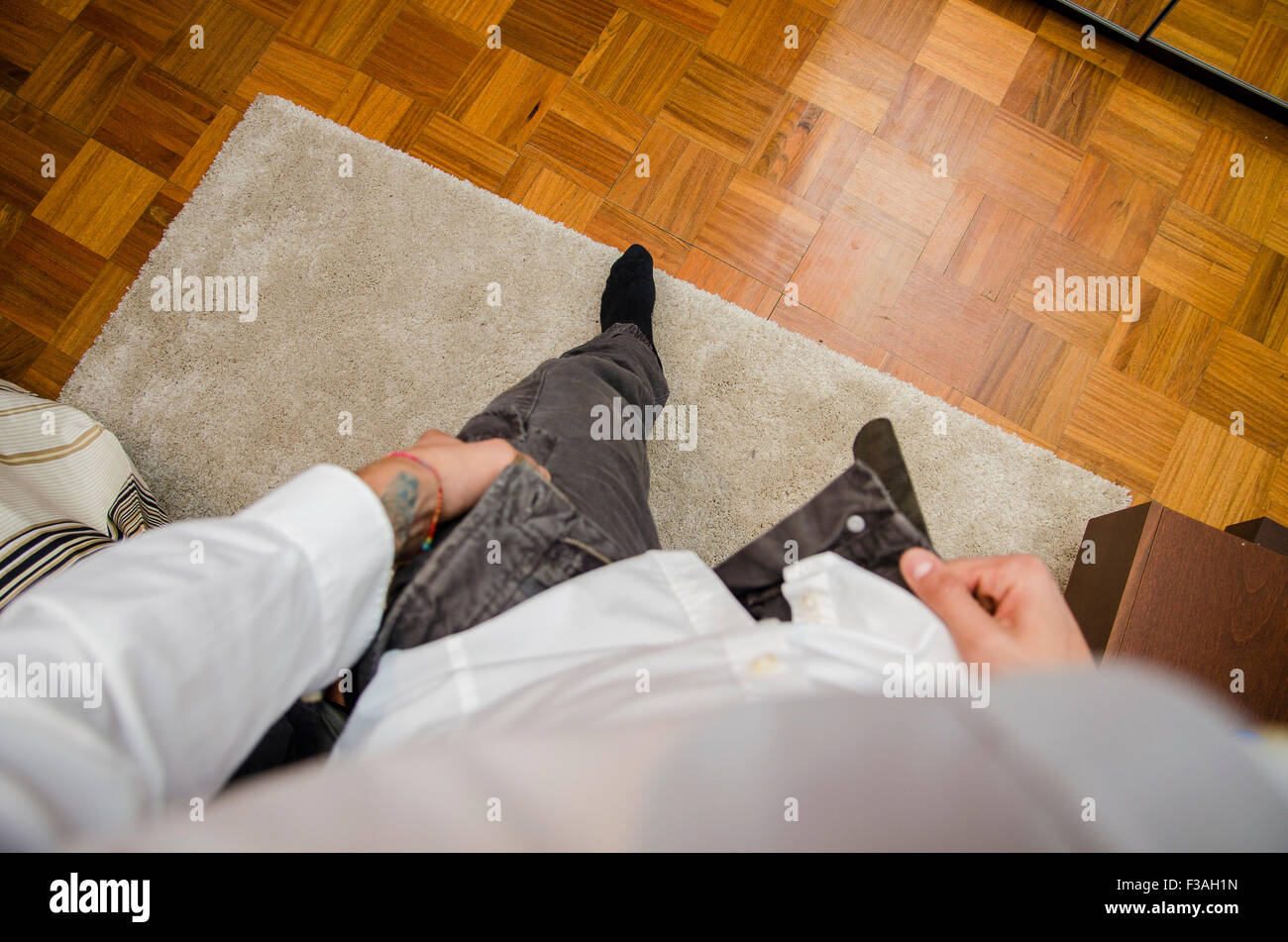 Man dressing standing in bedroom, dressing, putting pants on, first person point of view. Self POV - Stock Image