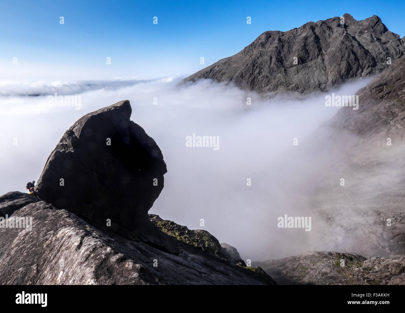 A climber abseiling off The Cioch in the Cuillin of Skye, Scotland. Cloud inversion below Stock Photo
