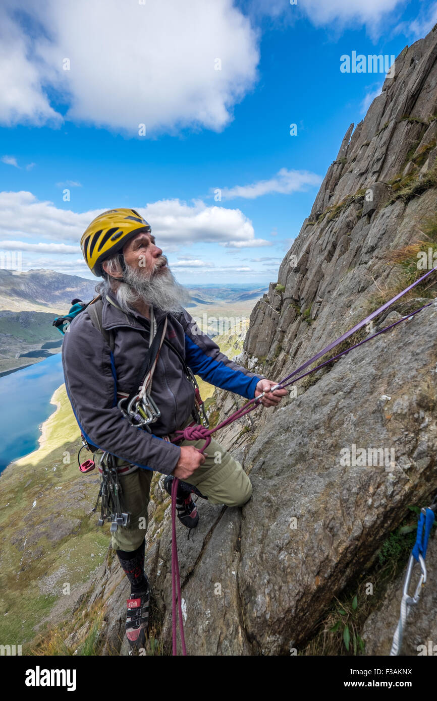 Retired man Rock climbing on Lliwedd, part of the Snowdon massif, Wales. The route is Avalanche/Red Wall/ Longlands Stock Photo
