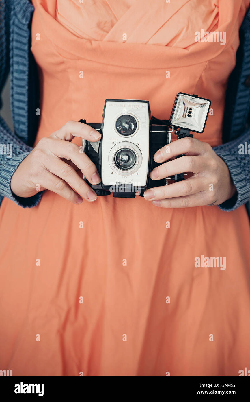 Vintage young woman holding an old camera - Stock Image