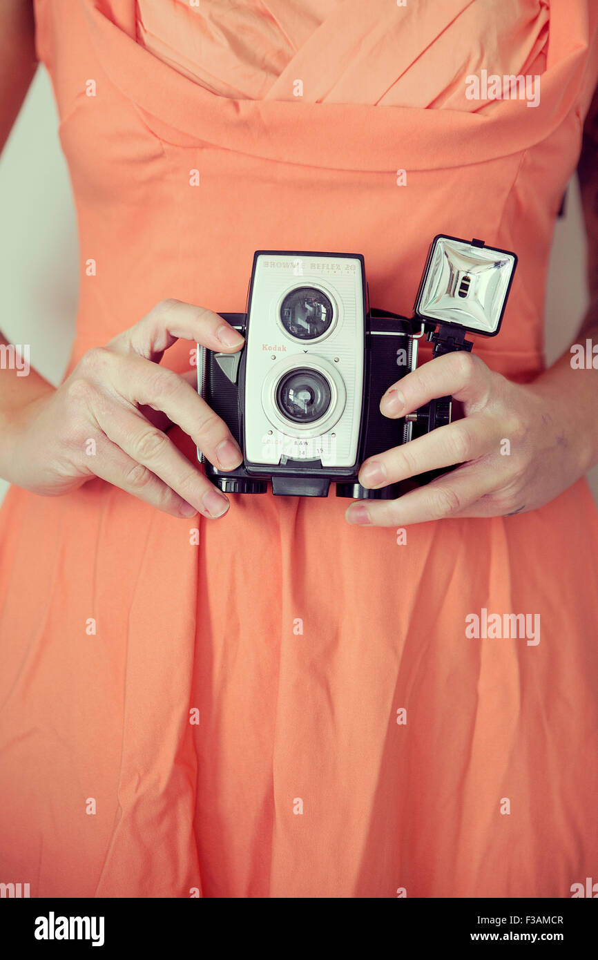 Young vintage woman holding a camera - Stock Image