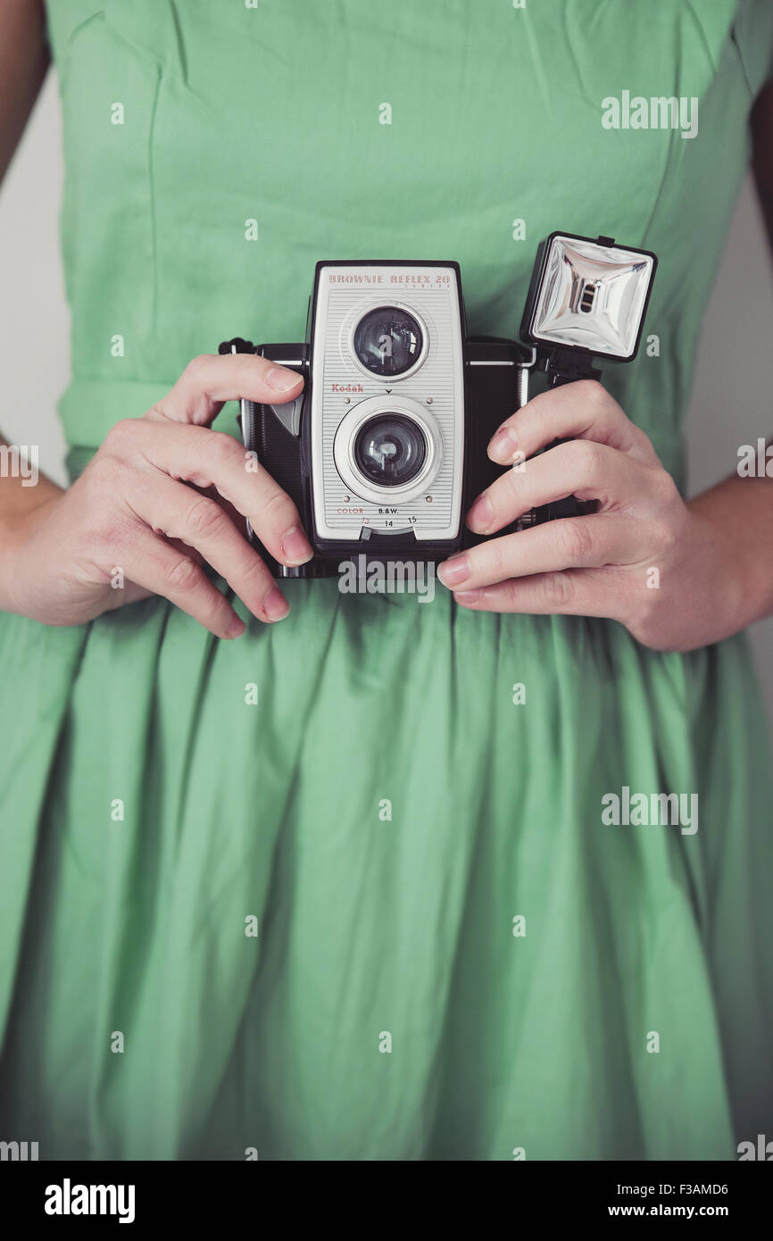 Vintage woman holding a vintage camera - Stock Image