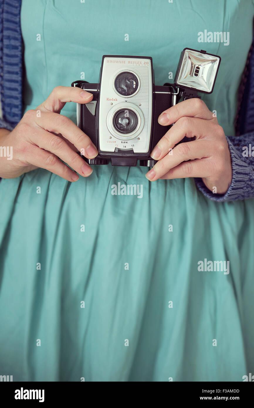 Vintage woman holding a vintage camera - Stock Image