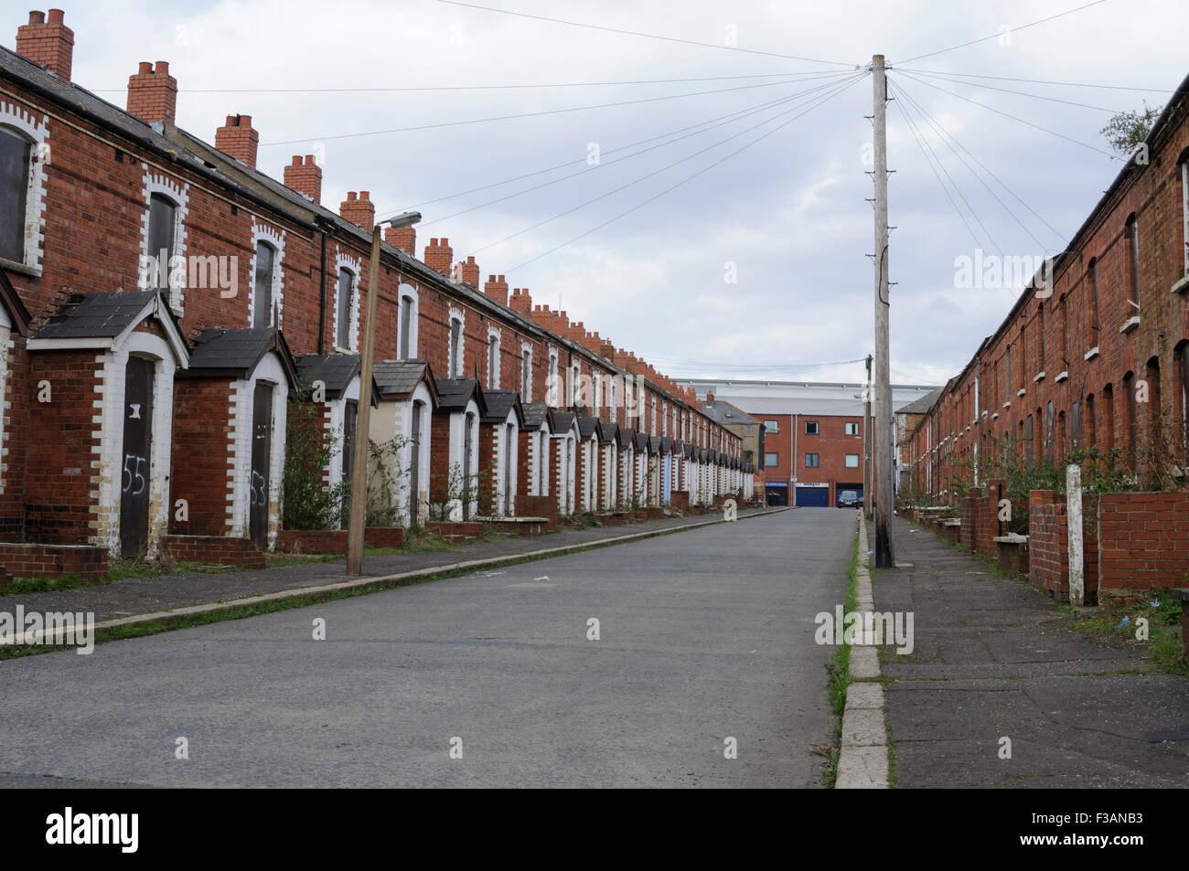Boarded up houses on a street in west Belfast - Stock Image