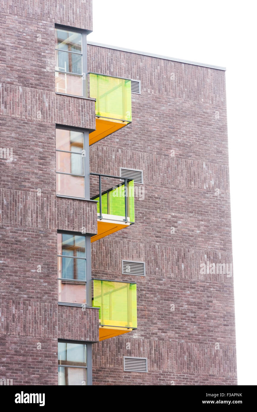 Residential building made of brown brick stones with colorful glass balconies - Stock Image