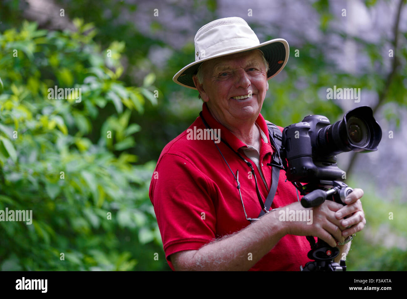 a26c0327fe8 Senior male wearing Tilley Hat holding camera smiling at photographer  blurred foliage background - Stock Image