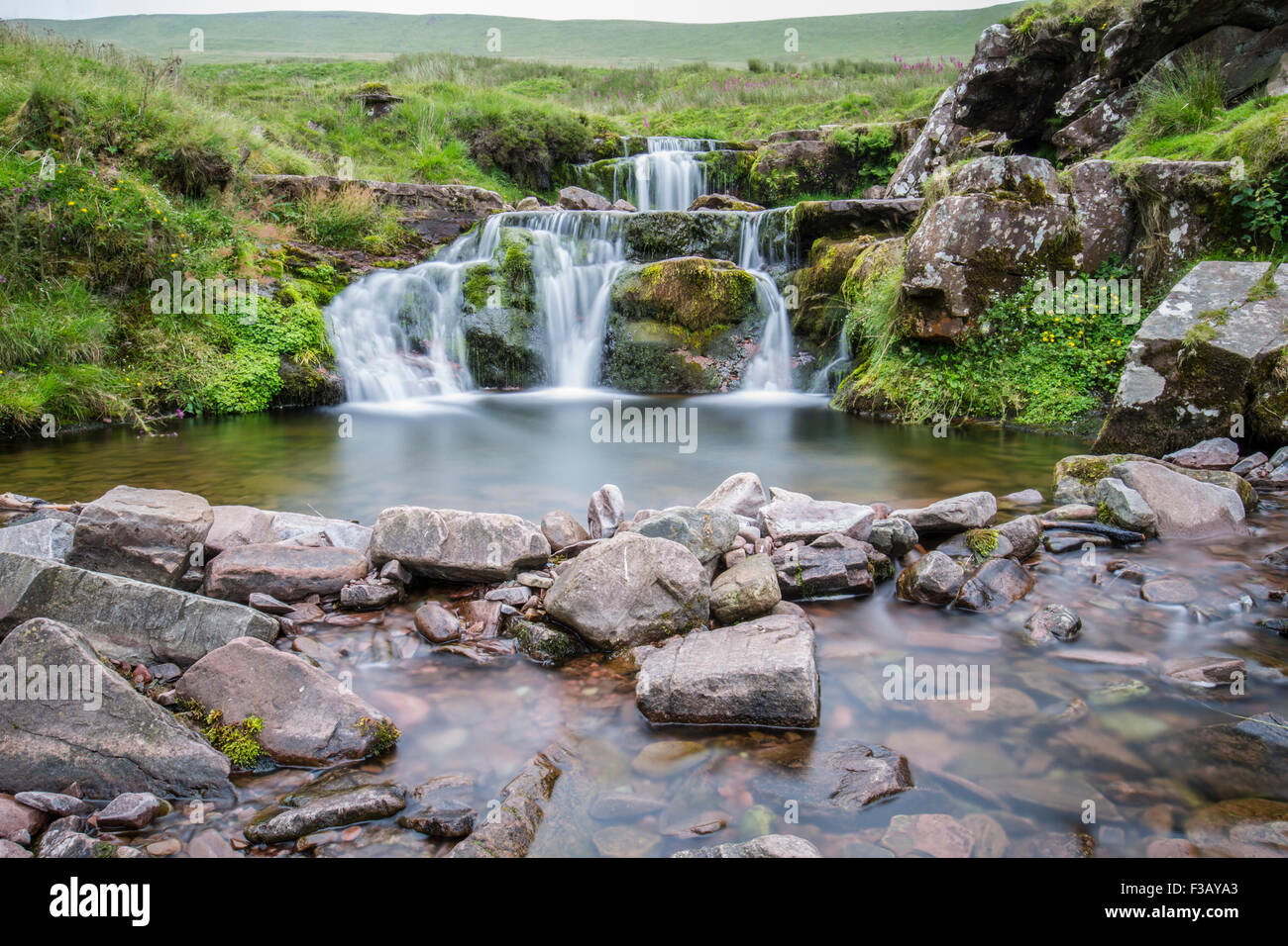 running water from the hills falling on rocks - Stock Image