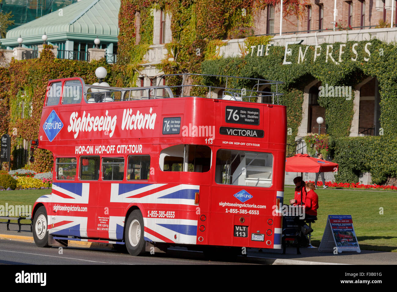 British red double deck tour bus open top in front of Empress Hotel Victoria British Columbia - Stock Image