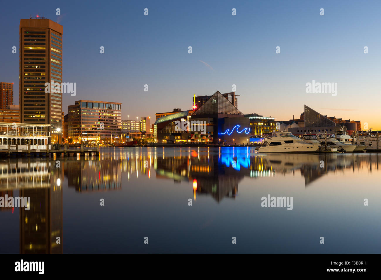 Baltimore skyline at dawn, including the World Trade Center and National Aquarium, reflected in the waters of the - Stock Image