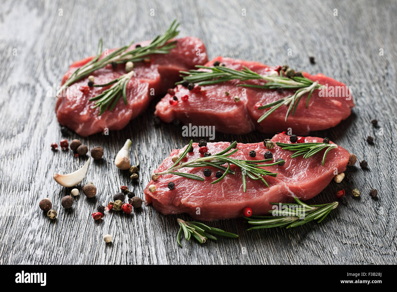 Three juicy raw beef steaks garnished with rosemary twigs, garlic and peppercorns - Stock Image