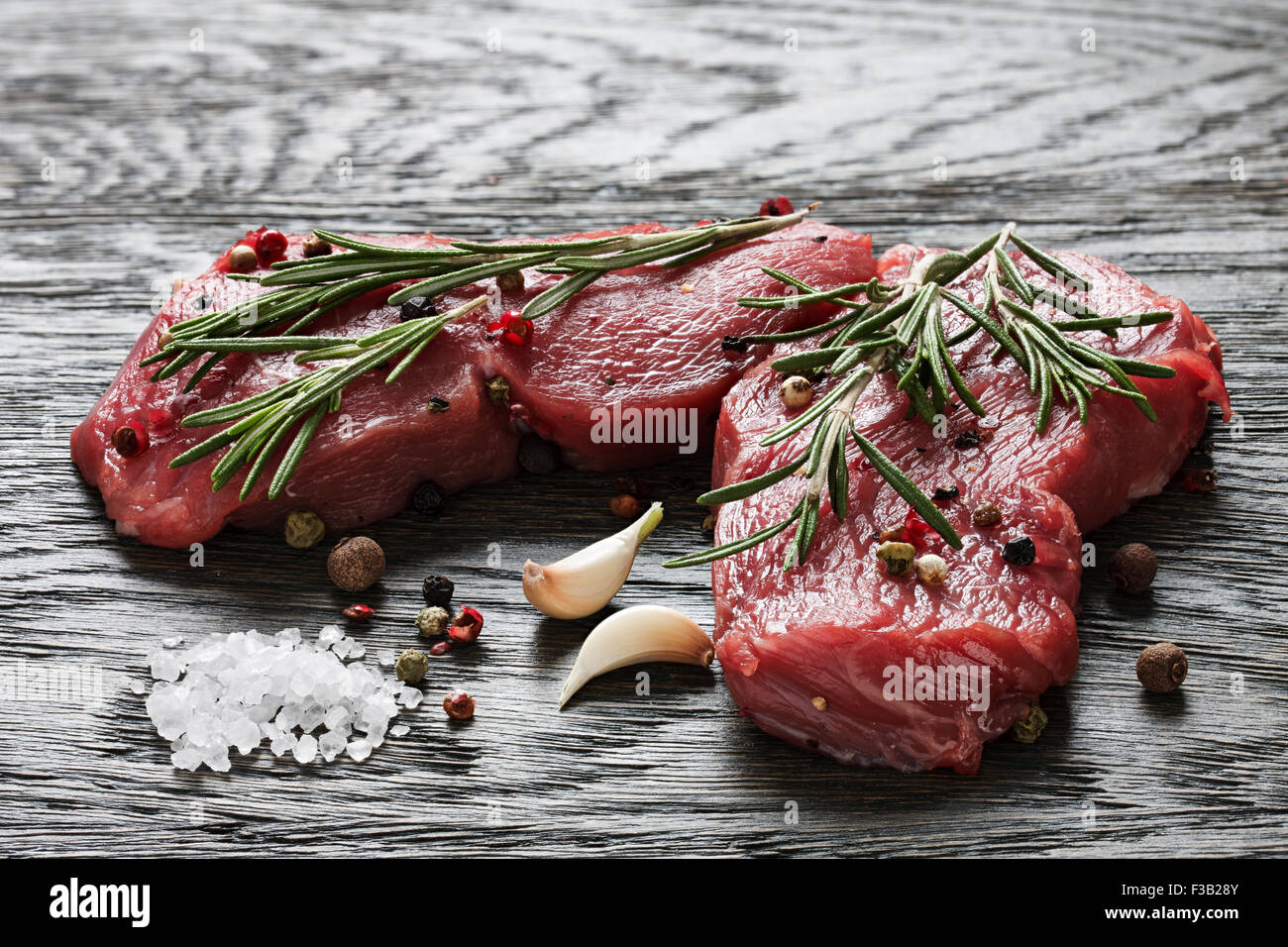 A couple of juicy raw beef steaks garnished with rosemary twigs, garlic and peppercorns - Stock Image