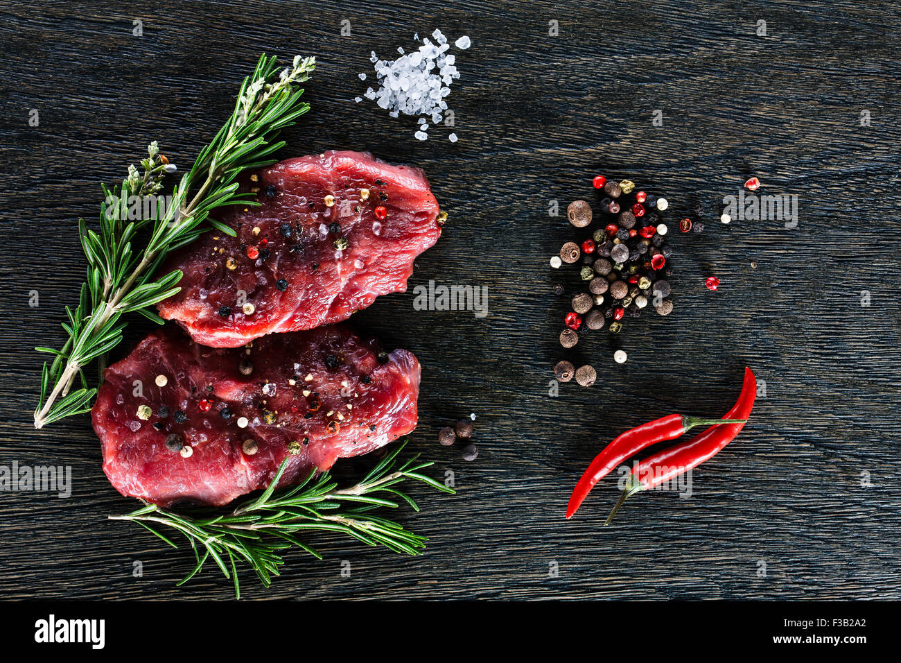 Two beef steaks garnished with a couple of rosemary twigs, dwarf chili peppers, sea salt granules and peppercorns Stock Photo