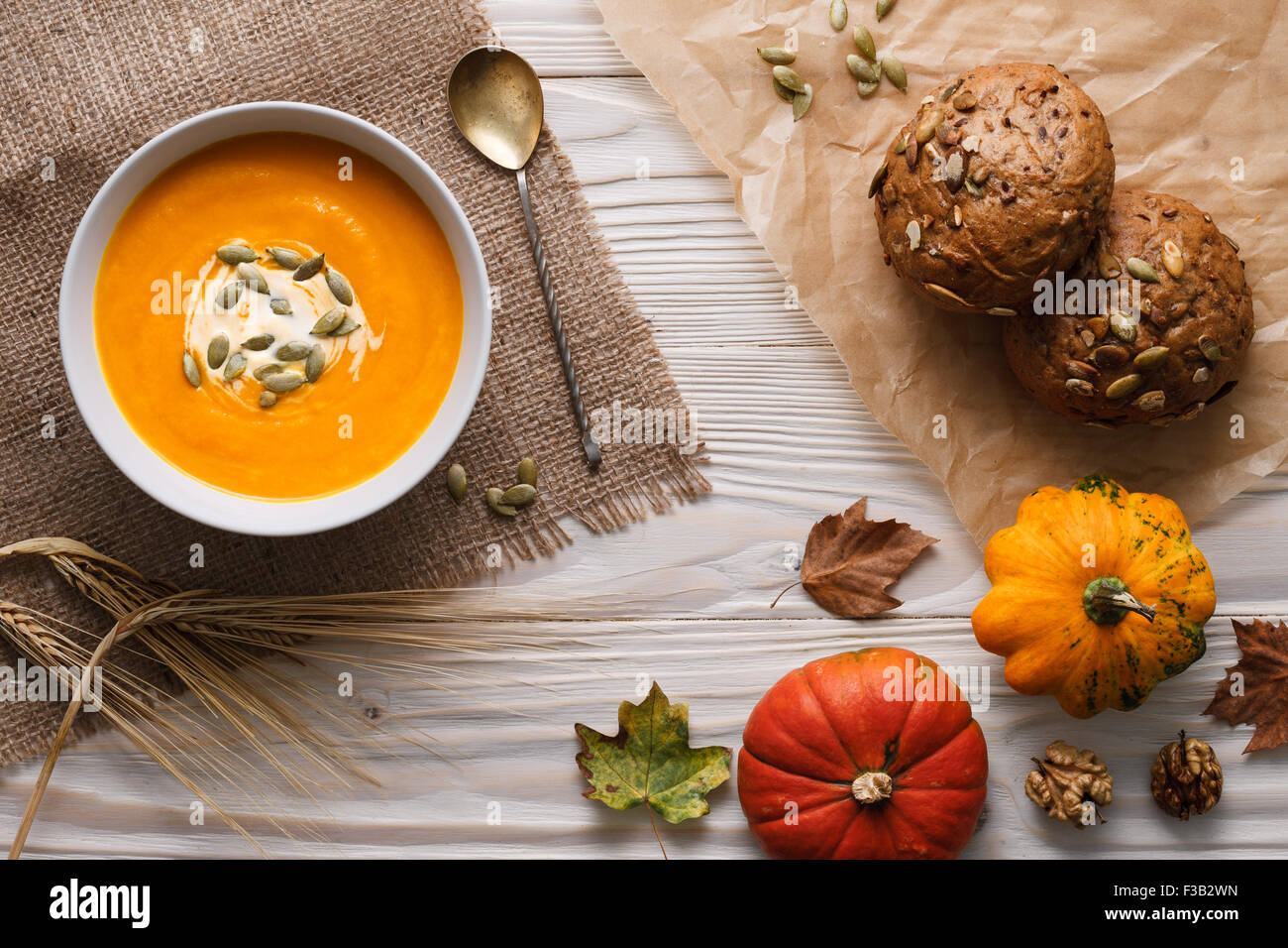 Traditional pumpkin soup with seeds and fresh just baked rye bans on a white wooden background. Stock Photo