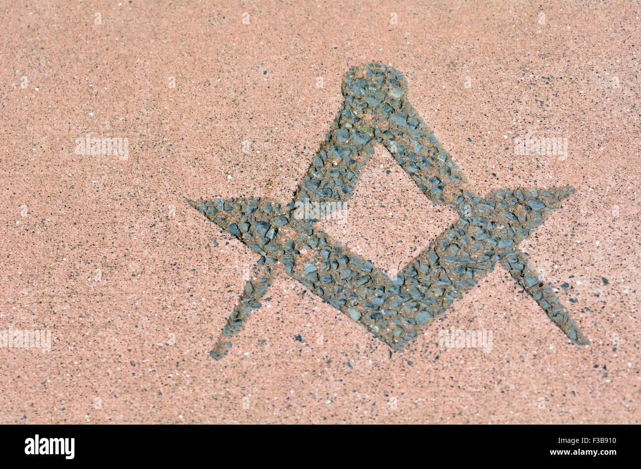 Freemasonry symbol made from stones on the ground. - Stock Image