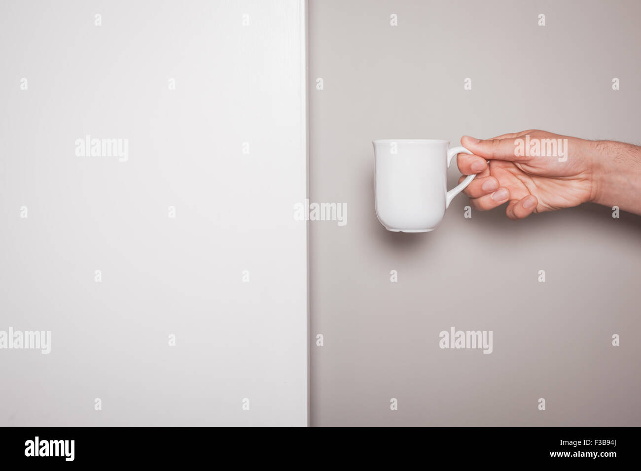 A Hand is holding a white cup against a green and white background - Stock Image